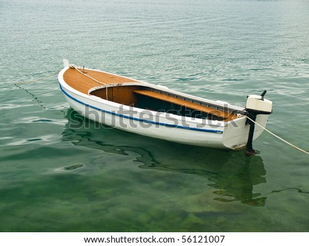 Single boat floating on a sea surface - stock photo