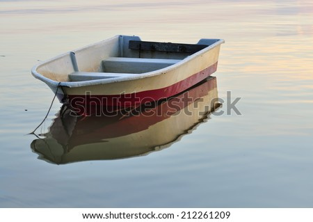 Single Boat In Calm Lake - stock photo