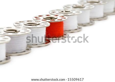 Single bobbin of bright red thread among many bobbins of white thread, on white background - stock photo