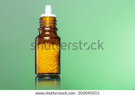 single bottle with homeopathy globules with green background. - stock photo