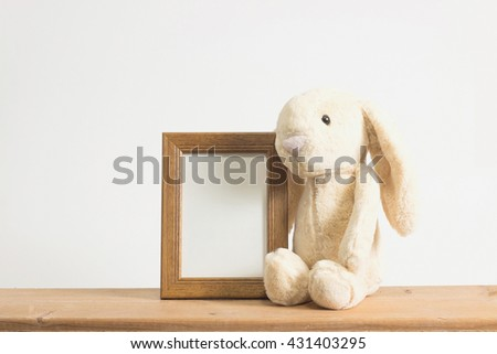 Single brown rabbit with photo frame on wooden table.  - stock photo