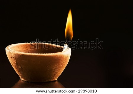 Single Burning Flame in an Earthen Lamp on a Black Background - stock photo