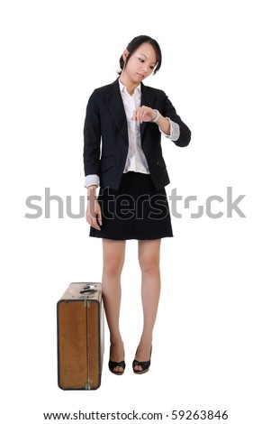 Single business girl waiting and watching time with old traveling case, full length portrait isolated on white background.