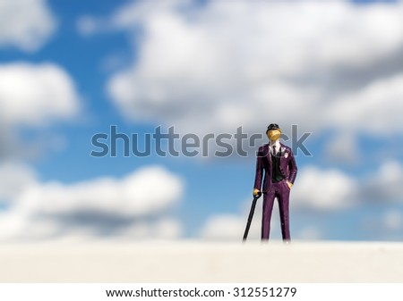Single business man miniature toy wearing a formal purple suit and holding a walking stick against a cloudy blue sky - stock photo