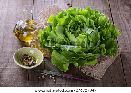 Single butter lettuce head, oil and seasoning over rustic wooden background - stock photo