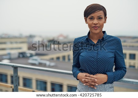 Single calm business woman with folded hands leaning against railing outside with overcast urban skyline and copy space in background - stock photo