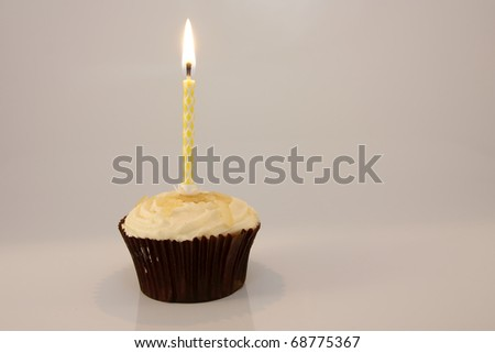 Single candle in lemon cupcake against a white background - stock photo