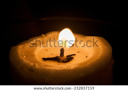 Single candle light illuminates a dark surrounding - stock photo