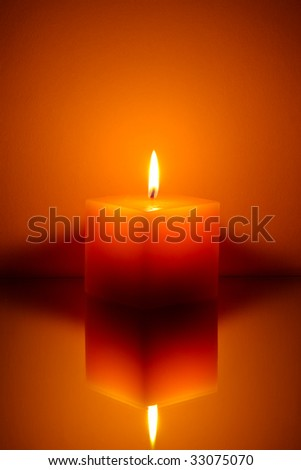 Single candle on orange background