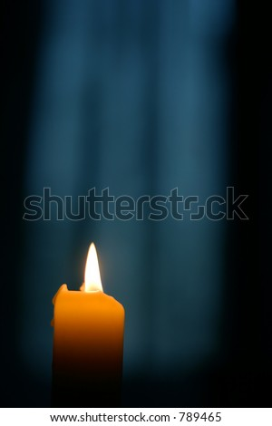single candle with blurred out dawn through curtains window - stock photo