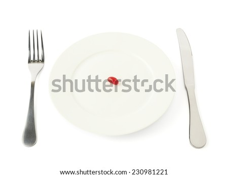 Single candy bean sweet in a white ceramic plate with the fork and knife next to it, composition isolated over the white background - stock photo