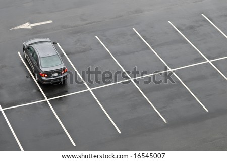 Single car in otherwise empty parking lot, in the rain - stock photo