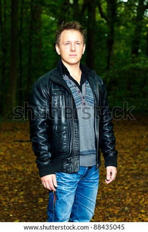 Single casual young man in forest. Short hair wearing jeans and black leather jacket. - stock photo