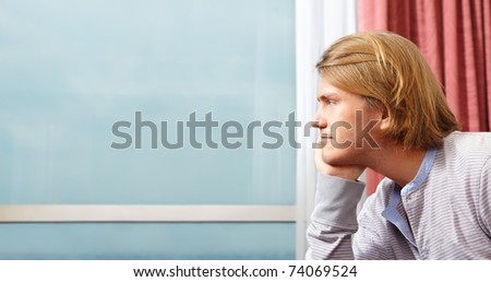 single caucasian man looking away through the window to blue sky as copy space area.