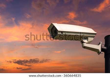 Single CCTV Security camera on beautiful sunrise sky and clouds background