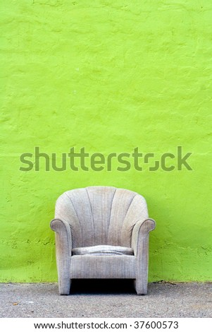 Single chair against green wall - stock photo