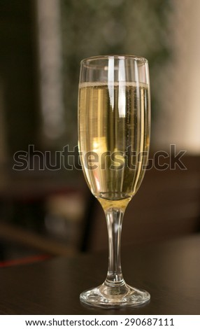 Single champagne flute with a brown wood background