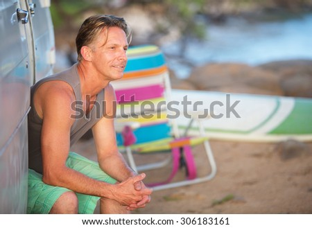 Single cheerful adult Caucasian male outdoors at beach - stock photo