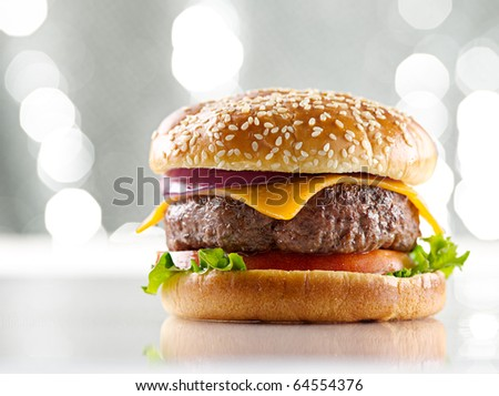 single cheeseburger with silver background and selective focus - stock photo