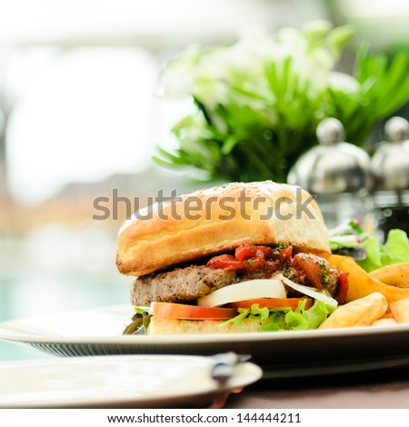 single cheeseburger with white background and selective focus - stock photo