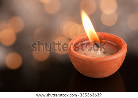 Single clay diya lamp with illumination and reflection. Indian celebration Diwali  with copy space - stock photo
