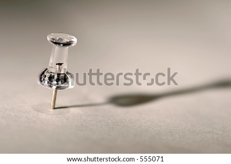 Single Clear Plastic Push Pin on White Background