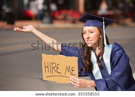 Single college graduate in gown holding hire me sign - stock photo