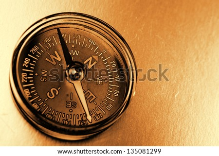 Single compass on brown background