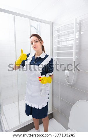 Single confident female domestic worker standing in blue dress and white apron with thumbs up gesture while holding spray bottle in bathroom - stock photo