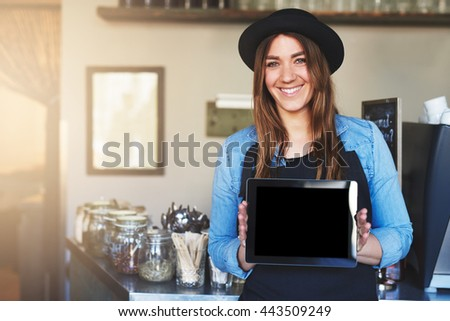 Single cute coffee house worker in hat and apron with cheerful expression holding blank tablet computer near counter - stock photo