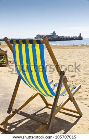 Single deck chair on the beach at Bournemouth, Dorset,UK with Bournemouth pier in the background - stock photo