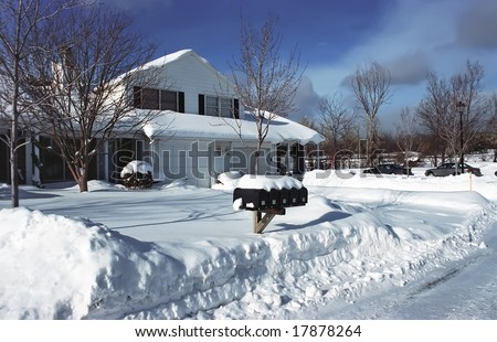 Single detached house on a sunny winter day. Snowed street after snow storm. - stock photo