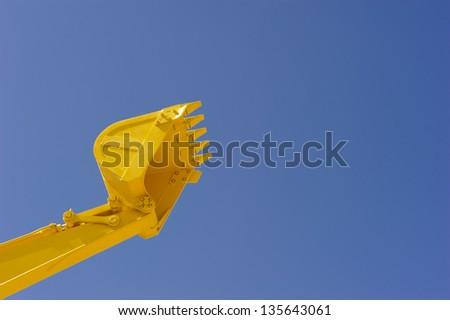 single digger shovel isolated on blue sky - stock photo