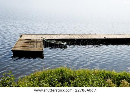 Single dilapidated boat moored to old cracked wood bridge at the Nidzkie lake in Ruciane-Nida, Masuria, Poland, Europe. Green grass coastal and reflections of sunlight on the water, horizontal  - stock photo