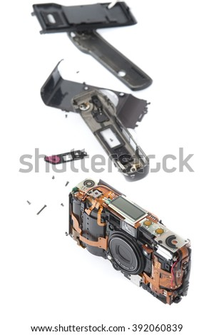 Single disassembled pocket camera with case pieces and exposed electronic parts over white background - stock photo