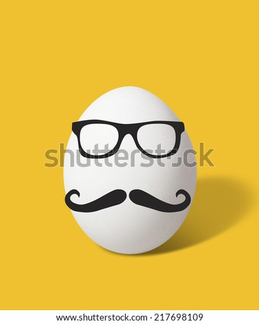 single egg with moustache and glasses in yellow background - stock photo
