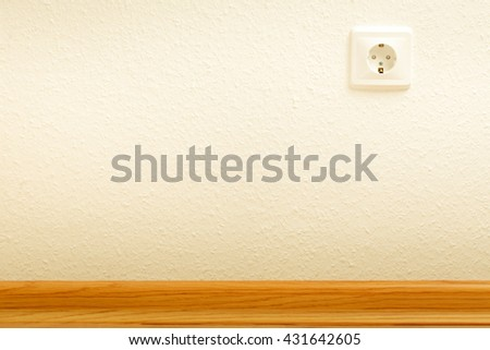 Single empty electric socket on white wall
