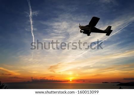 single engine airplane flying at sunset - stock photo