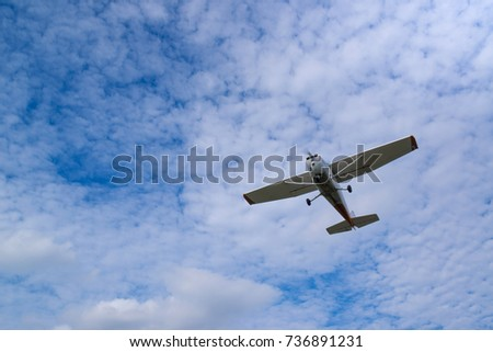 Single engine airplane in flight in blue sky against the background of clouds