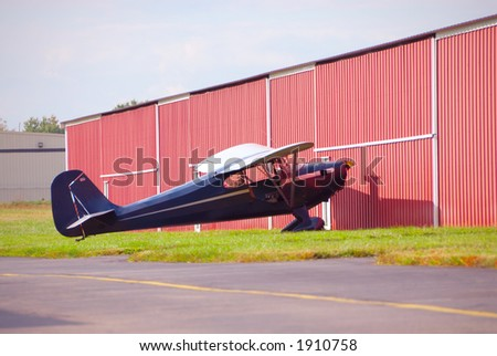 Single Engine Private Airplane - A single engine airplane sits outside the hangar at a small airport. - stock photo