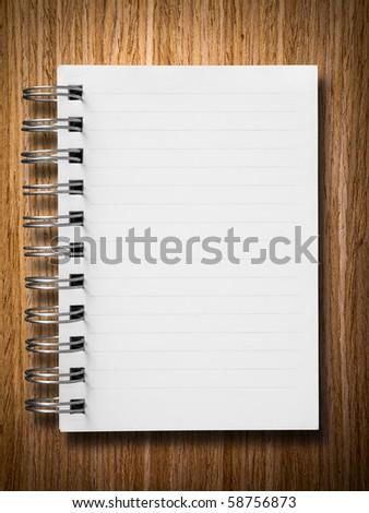 single face notebook on oak wood background - stock photo