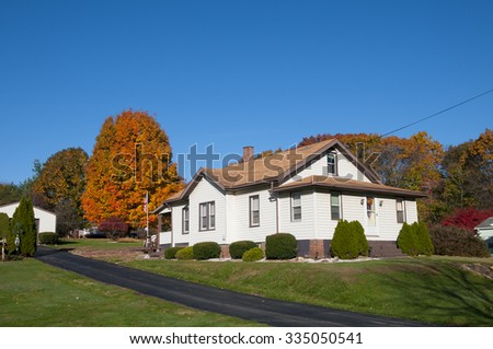 Single family dwelling on a hillside during the colorful fall season - stock photo