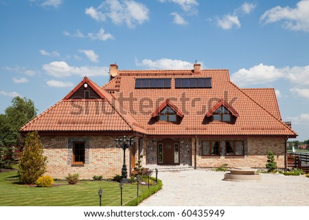 Single family house of brick with red roof over blue sky - stock photo
