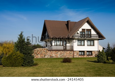 Single family small white house against blue sky - stock photo