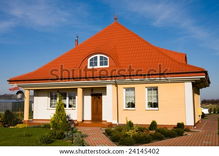 Single family small yellow house against blue sky - stock photo