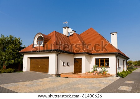 Single family white house with brown roof against blue sky - stock photo