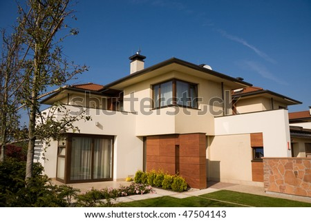 Single family yellow house over blue sky - stock photo