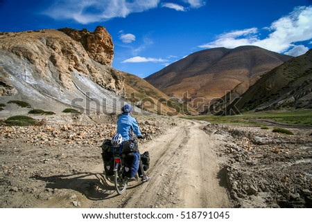 Single female cyclist on the bicycle on the remote road in Eastern Tibet