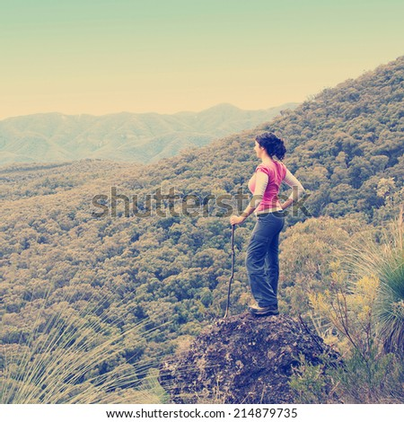 Single female hiker looks out at view in mountains with forest below her with Instagram style filter - stock photo