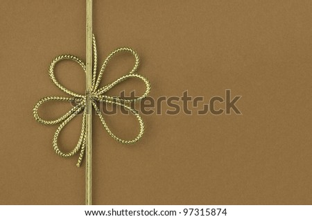 Single festive gold ribbon bow on plain brown background with room for your text - stock photo